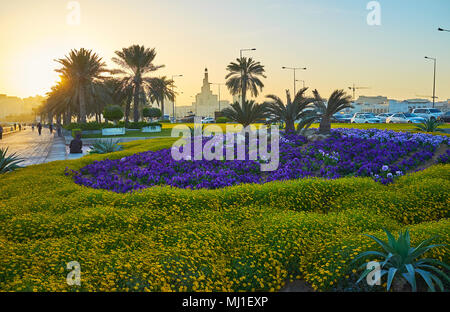 Enjoy the beautiful sunrise in seaside park of Doha with a view on Fanar spiral mosque behind the colorful flower beds and palm alley, Qatar.