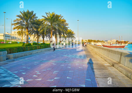 DOHA, QATAR - FEBRUARY 13, 2018: The morning in Corniche promenade with a view on walking people, dhow boats in Doha harbor and modern skyscrapers of