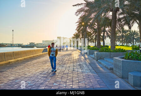 DOHA, QATAR - FEBRUARY 13, 2018: The morning in Corniche promenade with a view on walking people and dhow boats in Doha harbor, on February 13 in Doha