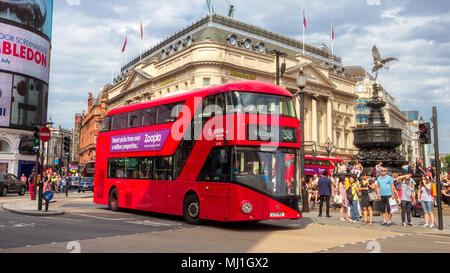LONDON - JUL 2, 2015: Red double-decker bus driving past Picadilly Circus in London. - Stock Photo