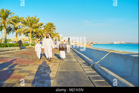 DOHA, QATAR - FEBRUARY 13, 2018: Arab family - father and sons in traditional dress walk along the Corniche promenade, on February 13 in Doha.
