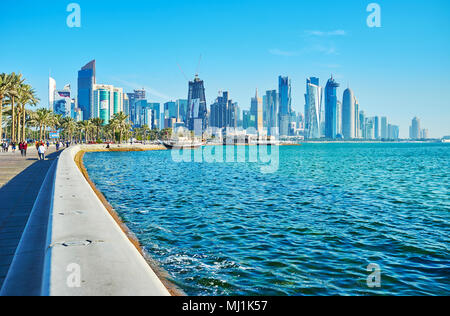 DOHA, QATAR - FEBRUARY 13, 2018:  The wave wall stretches along the Corniche promenade, protecting it and also serving as the bench for tired walkers, - Stock Photo