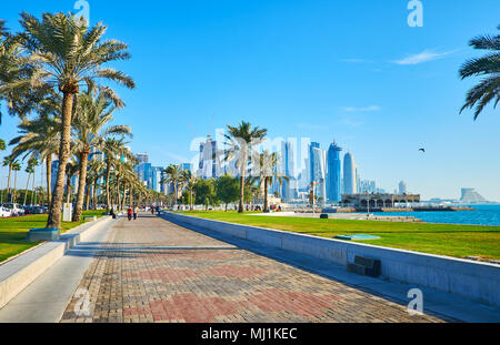 The beautiful seaside promenade with lush palms and juicy lawn stretches along the West Bay - the luxury business area in Doha, Qatar. - Stock Photo
