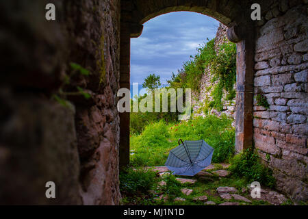 An umbrella of the color of the stormy sky on the border of an ancient stone portico - Stock Photo