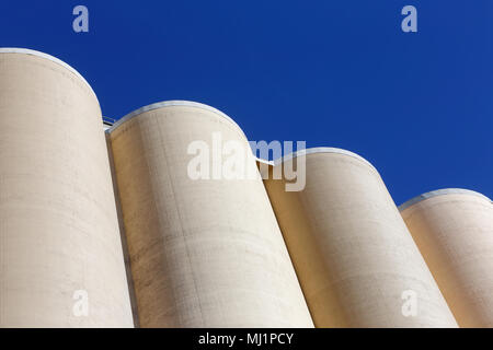 Top of cluster of silos used for storage of grain against a blue sky. - Stock Photo