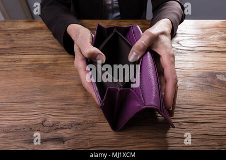 Close-up Of A Businessperson's Hand Holding Empty Purse Over Wooden Desk - Stock Photo