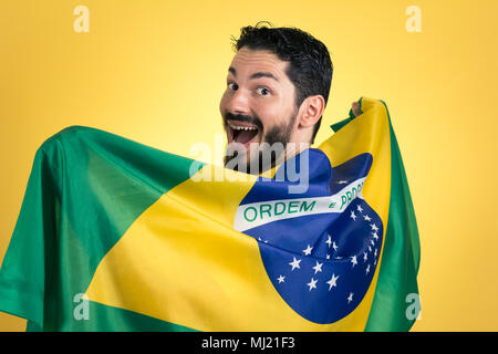 Brazilian soccer football team player. One supporter and fan holding Brazil flag. Wearing blue uniform on yellow backdrop. - Stock Photo
