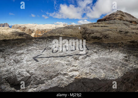 Pordoi mountains plateau in the Dolomites, with a written trail marker on a stone and the Piz Boe peak - Stock Photo