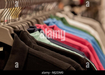 Colorful t-shirts on hangers. Men's stylish clothes. Showcase, sale, shopping. Fashion and trade concept - Stock Photo