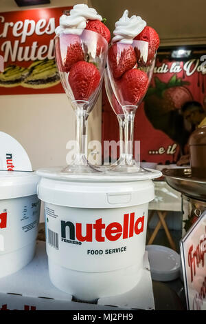 Fresh strawberries with whipped cream in two glasses, on Nutella chocolate jars on display at a kiosk stall. Summer season. - Stock Photo