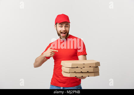 Delivery Concept: Handsome caucasian Pizza delivery man pointing finger. Isolated over grey background. - Stock Photo