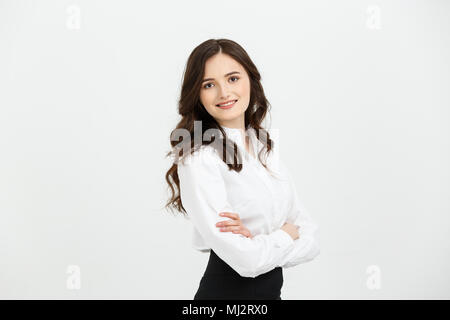 Businss Concept: Portrait confident young businesswoman keeping arms crossed and looking at camera while standing against grey background - Stock Photo