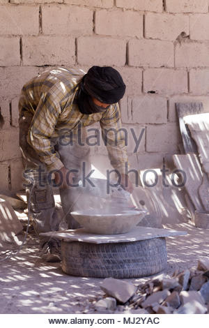Workers create table top surfaces and ornaments with natural rock fossil patterns using stone found in the Erg Chebbi and Foum Zguid region of the Mor - Stock Photo