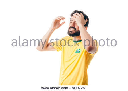 Unhappy Brazilian soccer or football player with palm on his face on white background - Stock Photo