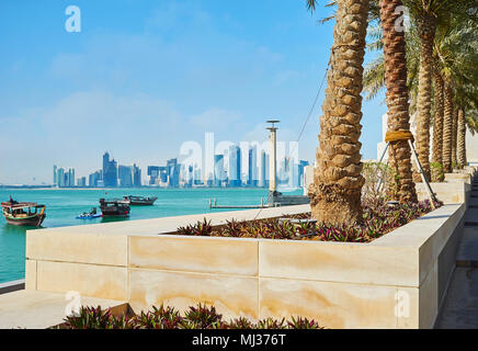 The palm alley along the way to Museum Island with a view on coast of Persian Gulf and modern architecture of business district, Doha, Qatar.