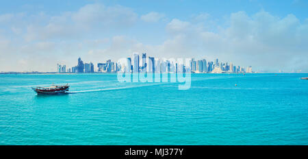 DOHA, QATAR - FEBRUARY 13, 2018: The seascape of Persian Gulf with iconic skyline of Doha - glass and metal skyscrapers of West Bay neighborhood, on F - Stock Photo