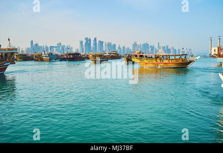 DOHA, QATAR - FEBRUARY 13, 2018: The numerous old wooden dhows are moored in harbor, this tourist fleet attracts people to enjoy sea trips, on Februar - Stock Photo