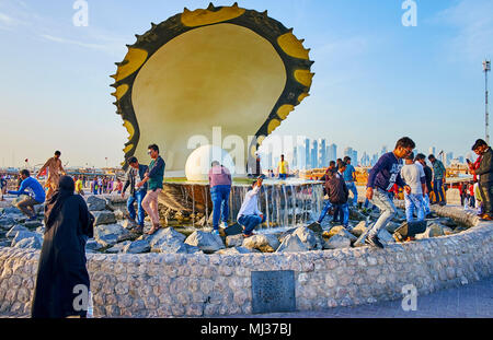 DOHA, QATAR - FEBRUARY 13, 2018: People make selfies and watch the Pearl fountain, located on Corniche Promenade, on February 13 in Doha. - Stock Photo
