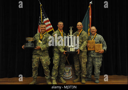 Iowa National Guard (IANG) team poses with their portion of the spoils from the 2018 U.S. Army Small Arms Championships Mar. 11-17, 2018 at Ft. Benning, Ga. As a team, IANG placed 2nd Overall Small Arms Team Champions and 1st  Overall Service Rifle Team Champions. Left to right: Army National Guard Sgt. Karl Johnk, Army National Guard Staff Sgt. Tyson Fisher, Army National Guard Sgt. 1st Class Paul Deugan,  Air National Guard Tech. Sgt. Micah Larson.('Released' U.S. National Guard Image collection celebrating the bravery dedication commitment and sacrifice of U.S. Armed Forces and civilian per - Stock Photo