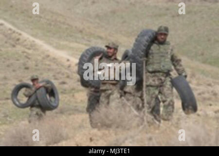Afghan National Army Commando Qualification Course Class 24 conducts improvised physical training consisting of tire carries up a 1 km hill at the ANASOC School of Excellence near Kabul, Afghanistan, Mar. 18, 2018. 'Building functional strength and endurance is vital to becoming a Commando,' an ANASOC mentor stated. 'Tough physical conditioning is the foundation of the elite Commando mindset.' CDOQC is a 14-week course designed to assess and train Afghan soldiers for assignment in one of the ten Special Operations Kandaks (Battalions). More than 4,000 new Commandos will join the regionally ali - Stock Photo