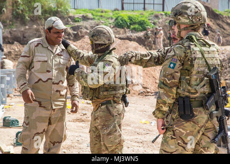 British soldiers deployed in support of Operation Inherent Resolve, talk with an Iraqi security force member during the building of a bridge in Mosul, Iraq, March 20, 2018. The United Kingdom Bridge Training Team advises and assists Iraqi security forces in construction of an Acrow Poseidon bridge over the Tigris River. This effort is part of Combined Joint Task Force – Operation Inherent Resolve, the global Coalition to defeat ISIS in Iraq and Syria. (U.S. Army Image collection celebrating the bravery dedication commitment and sacrifice of U.S. Armed Forces and civilian personnel.