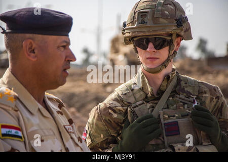 A British soldier, deployed in support of Operation Inherent Resolve, discusses the construction of a bridge with an Iraqi security force (ISF) member in Mosul, Iraq, March 21, 2018. The United Kingdom Bridge Training Team advises and assists ISF in the construction of an Acrow Poseidon bridge over the Tigris River. This effort is part of Combined Joint Task Force – Operation Inherent Resolve, the global Coalition to defeat ISIS in Iraq and Syria. (U.S. Army Image collection celebrating the bravery dedication commitment and sacrifice of U.S. Armed Forces and civilian personnel.