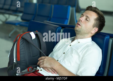 Caucasian man is sleeping in lounge area at the airport. - Stock Photo