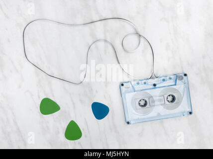 Blue audio tape and guitar picks on marble background. - Stock Photo