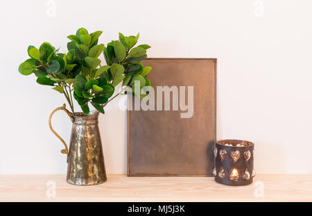 Vintage style home decor composition. Metal frame with copy space, ficus in antique jar and candle.