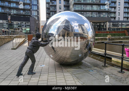 A Reflective Approach is a two-part sculpture consisting of 2 life-size bronze figures pushing two reflective stainless steel spheres towards a canal. - Stock Photo