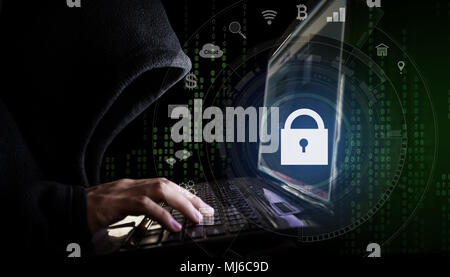 Internet network security system. Hacker in black hoodie using computer laptop and technology lock and application icons - Stock Photo