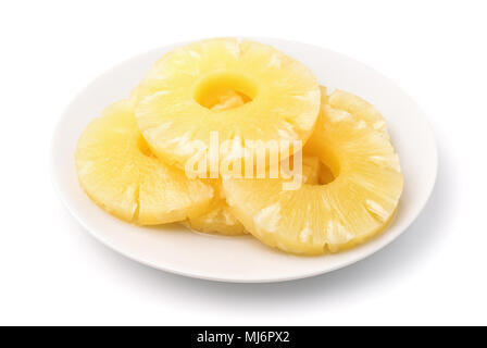 Canned pineapple slices on plate isolated on white - Stock Photo