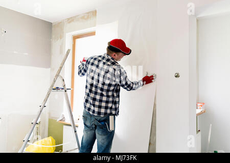 Glueing wallpapers at home. Young man, worker is putting up wallpapers on the wall. Home renovation concept - Stock Photo