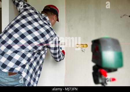 lueing wallpapers at home. Young man, worker is putting up wallpapers on the wall. Home renovation concept - Stock Photo