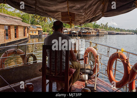 Alappuzha, Kerala / India - April 15 2018: A captain is steering a house boat through the waterways of Alappuzah. - Stock Photo