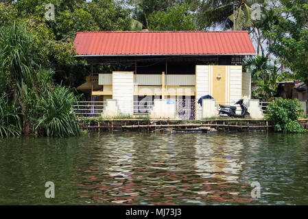Alappuzha, Kerala / India - April 15 2018: A modern Indian house on the banks of the waterways of Alappuzha reflected in the water. - Stock Photo