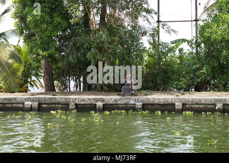 Alappuzha, Kerala / India - April 15 2018: An elderly woman is fishing alone with a line in the waterways of Alapuzzha. - Stock Photo