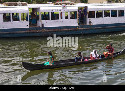 Alappuzha, Kerala / India - April 15 2018: A man is paddling a wooden boat with his family while a fast motor powered commuter boat is going past it. - Stock Photo