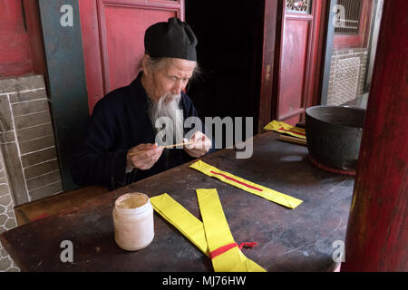 Monk working in temple near Water Curtain Cave or Shuilian Dong. Luomen, Gansu province, China, Asia - Stock Photo