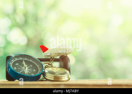 Travel background concept. Small airplane with gold watch and compass on wood table with blurred tree  and sunlight background. Picture for add text m - Stock Photo