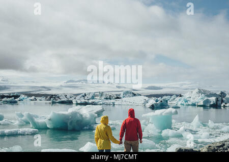 romantic Tourists couple in Iceland near glacial lagoon . - Stock Photo