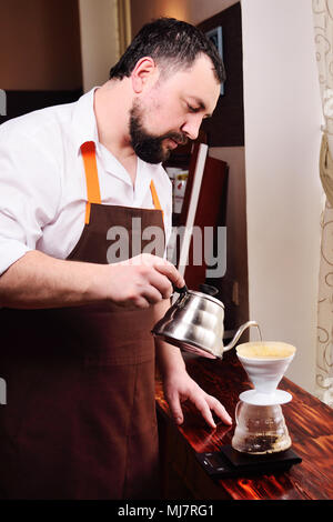 barista or coffee barman prepares coffee by an alternative method of brewing - pour over - Stock Photo