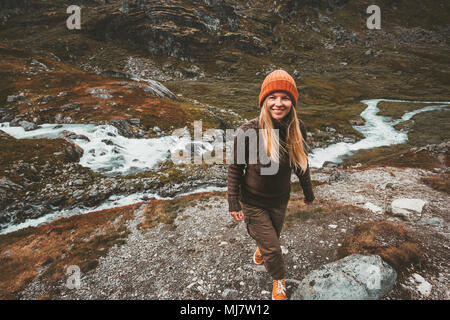 Happy young woman walking alone in scandinavian mountains Travel adventure lifestyle concept active vacations in Norway - Stock Photo
