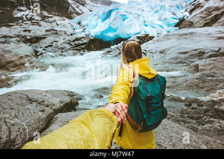 Couple travelers follow holding hands in  mountains glacier love and Travel lifestyle concept active adventure hiking vacations in Norway wild nature - Stock Photo