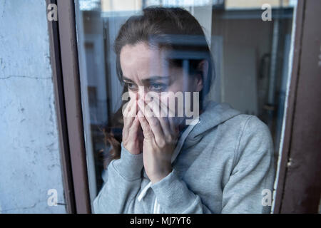 Close up portrait of middle aged latin woman sad and depressed looking through the window refection, thinking about her life suffering depression in m - Stock Photo