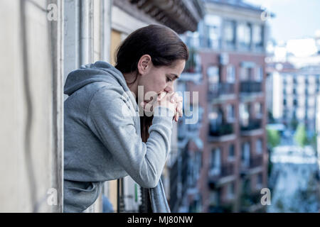 young Latin. sad and depressed woman standing on a balcony feeling over overwhelmed and suffering depression in mental health concept - Stock Photo