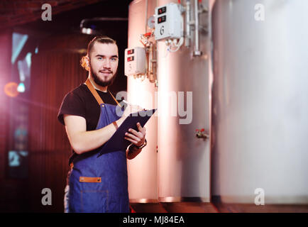 bearded brewer man on a background of beer tanks and a brewery making notes in a tablet - Stock Photo