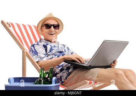 Old tourist with a laptop sitting in a deck chair next to a cooling box and looking at the camera isolated on white background - Stock Photo