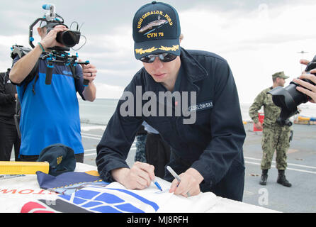 NORFOLK, Va. (April 19, 2018) --  NASCAR driver Brad Keselowski signs a Charlotte Motor Speedway flag during a tour onboard USS Gerald R. Ford (CVN 78). Keselowski will be representing the U.S. Navy and the USS Gerald R. Ford (CVN 78) at the Coca-Cola 600 race in Charlotte, North Carolina on Memorial Day weekend. (U.S. Navy photo by Mass Communication Specialist 3rd Class Cat Campbell) - Stock Photo