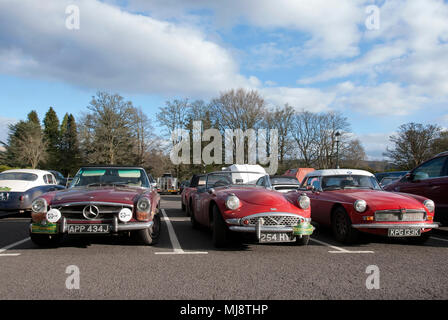 Mercedes Benz Daimler Dart and MGB Sports Cars front view of 1970 Maroon Mercedes Benz 280SL 1960 Red Daimler Dart SP250 1972 Red and White MGB Roadst - Stock Photo